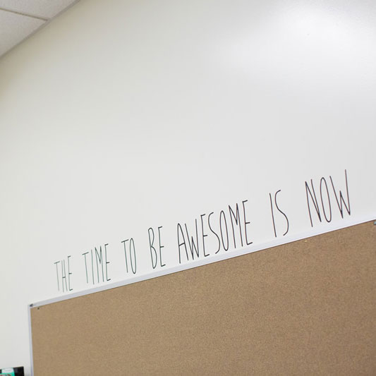 Classroom wall with a phrase reading: the time to be awesome is now