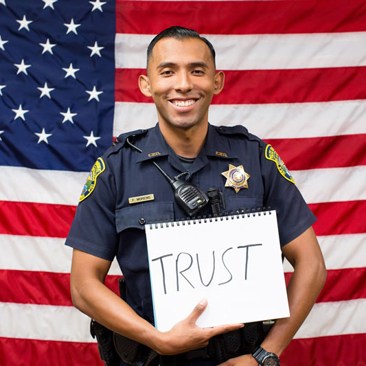 Police officer with the American flag behind him holding an oversized card reading: trust