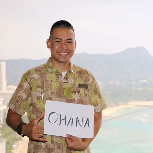 Man with a colorful shirt with Waikiki Beach behind him, holding an oversized card reading: ohana