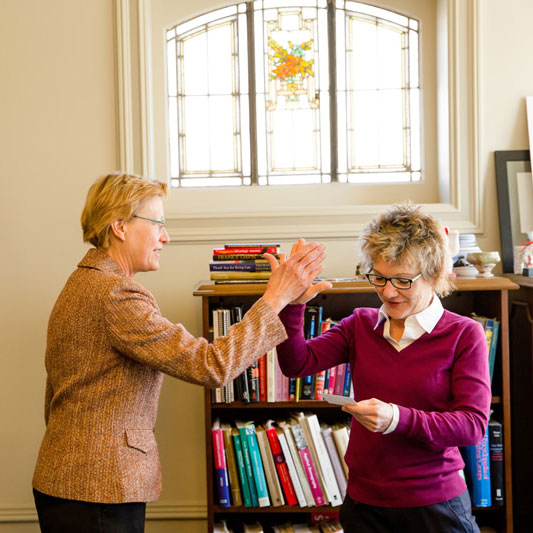 President Mary Daly high-fiving a community leader