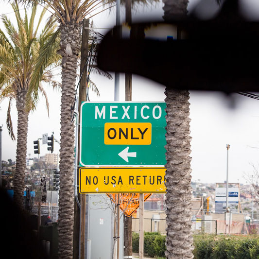 Street sign reads: Mexico only, no USA return