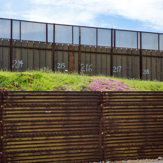 Rusted metal fence at U.S.-Mexico border